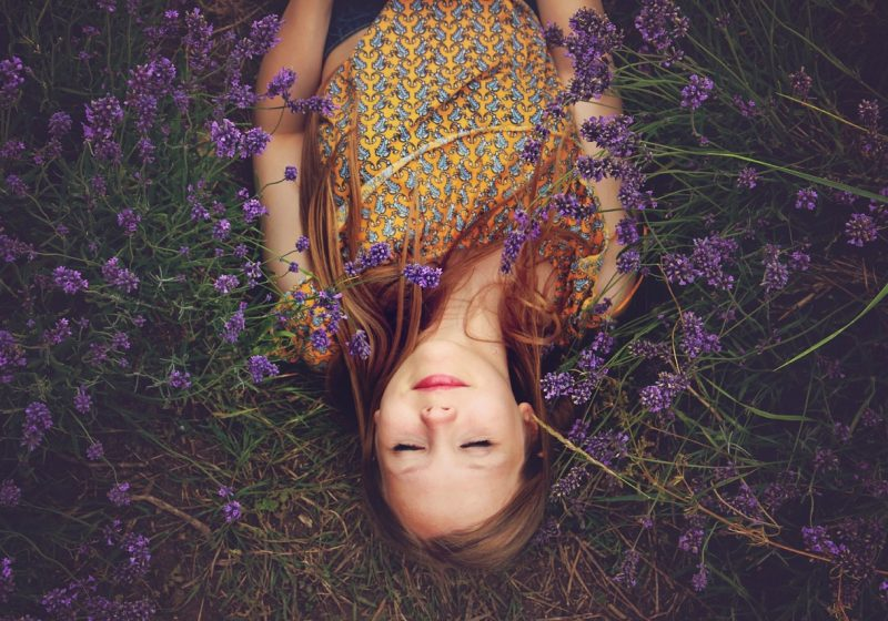 Woman laying on the earth wrapped in scarf surrounded by flowers woman's clothing protection wise fashion| The Sublime Woman