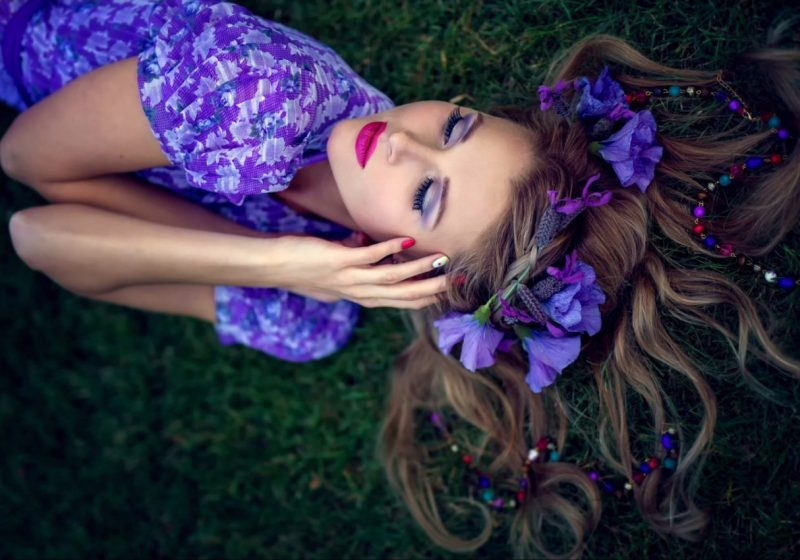 Practice Woman's Sahasrara Chakra Healing beautiful woman in violet laying on the earth with purple flowers | The Sublime Woman