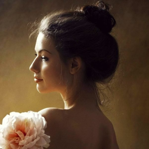 Feminine Stress Relief Stress and Femininity beautiful young woman smiling with a flower   The Sublime Woman