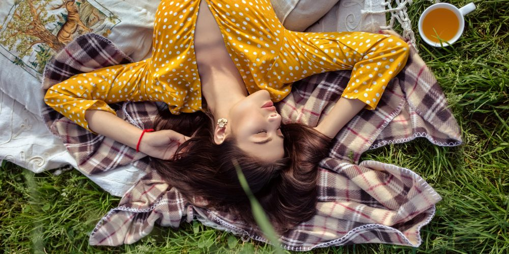 Dangers Of Woman's Desire To Help, Depletion From Too Much Helping, Beatiful Woman laying relaxing on Eart Green garss yellow dress, The Sublime Woman